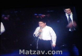 A soloist from the new Pirchei choir singing. At right is Yossi Newman.