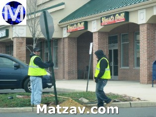 Workers restore a stop sign at Yussi's in West Gate.