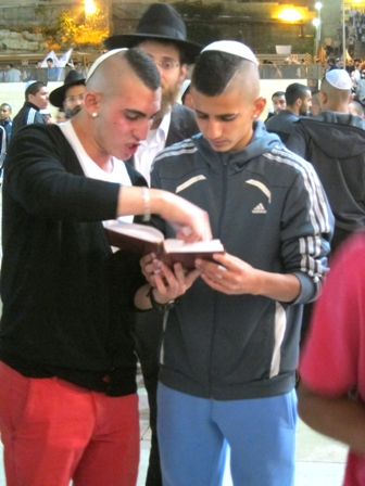 An older Shalom L'am boy shows a younger boy how to daven.