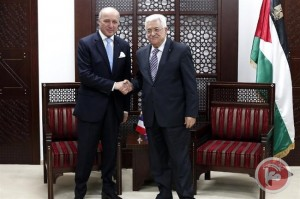 French Foreign Minister Laurent Fabius (L) shakes hands with President Mahmoud Abbas