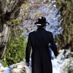 An Ultra-Orthodox Jewish man walks on a snow-covered street near Jerusalem's Old City