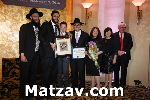 Mr. and Mrs. Elisha Hisinger anf family receiving the Chazaq Keter Torah Award