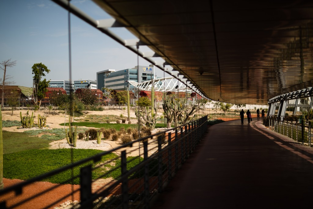People are silhouetted as they stroll along a shaded walkway connecting Ben-Gurion University of the Negev to Gav-Yam Negev Advanced Technologies Park via a bridge in Beersheba, Israel. Must credit: Photo by David Vaaknin for The Washington Post