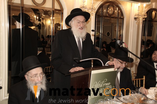 rav yisroel belsky speaking at previous mifal event and rav moshe wolfson on dais